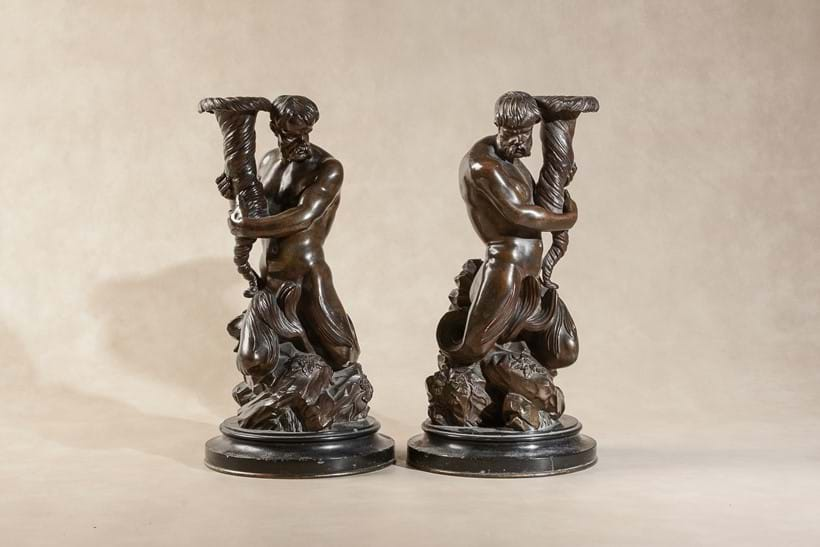 Inline Image - LOT 119: A PAIR OF PATINATED BRONZE FIGURAL CANDELABRA BASES CAST AS TRITONS, INSPIRED BY BERNINI AND TEDESCO AND AFTER DESIGNS BY JOSIAH WEDGWOOD AND MATTHEW BOULTON, FIRST QUARTER 19TH CENTURY | EST. £1,000-1,500 (+FEES)