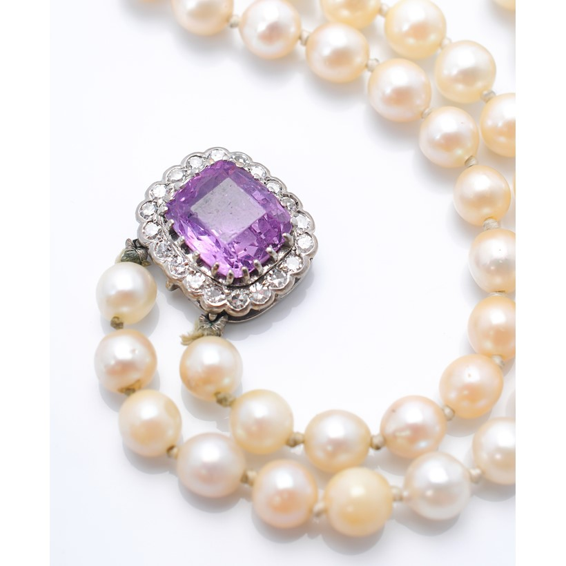 Inline Image - An early 20th century cushion shaped pink/purple sapphire set in a pearl necklace clasp. Sold at Dreweatts for £2,750