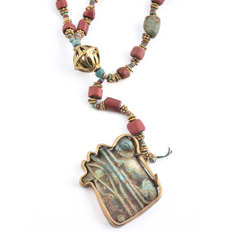 Inline Image - An Egyptian Revival coral and blue faience bead necklace, the barrel shaped coral beads and faience beads interspersed with granulated gilt metal rondels, suspending an Egyptian style blue composite amulet, the plaque carved to depict a reclining lion and the Eye of Horus, one drop missing, 38cm long
