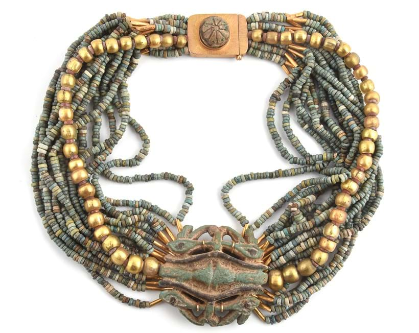 Inline Image - An Egyptian Revival blue faience bead collar necklace, composed of sixteen rows of spacer beads and a gold coloured glass bead row, supporting a blue faience amulent with the Eyes of Horus, on a plaque clasp applied with a carved motif, 40cm long