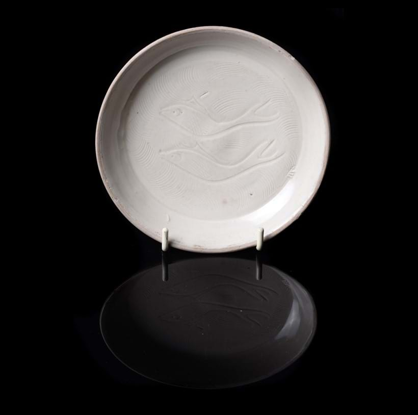 Inline Image - Lot 291: A rare small Chinese Ding style 'Twin Fish' dish, Song Dynasty, Provenance: John Sparks Ltd, 128 Mount Street, London until presumably sold to the late vendor in 1988 and by family descent. The Estate of Christopher and Rosemary Warren. | Est. £400-800 (+fees)